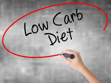 low carb diet: Woman Hand Writing Low Carb Diet with black marker over transparent board. Isolated on grey. Business concept. Stock Photo