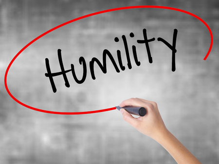 humility: Woman Hand Writing Humility  with black marker over transparent board. Isolated on grey. Business concept. Stock Photo Stock Photo