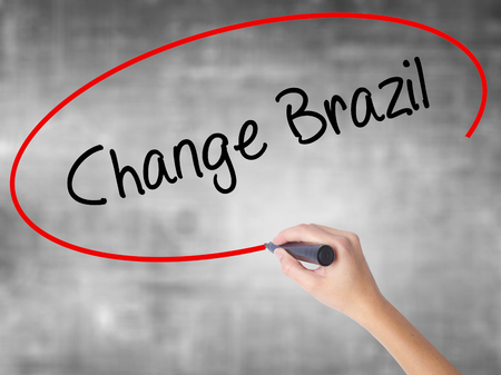 Woman Hand Writing Change Brazil  with black marker over transparent board. Isolated on grey. Business concept. Stock Photo Stock Photo