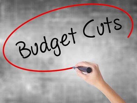 Woman Hand Writing Budget Cuts with black marker over transparent board. Isolated on grey. Business concept. Stock Photo
