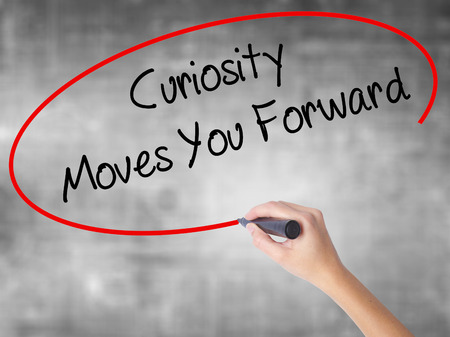 faq's: Woman Hand Writing Curiosity Moves You Forward with black marker over transparent board. Isolated on grey. Business concept. Stock Photo