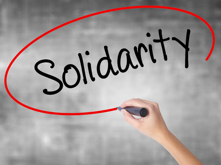 Woman Hand Writing Solidarity  with black marker over transparent board. Isolated on grey. Business concept. Stock Photo Stock Photo