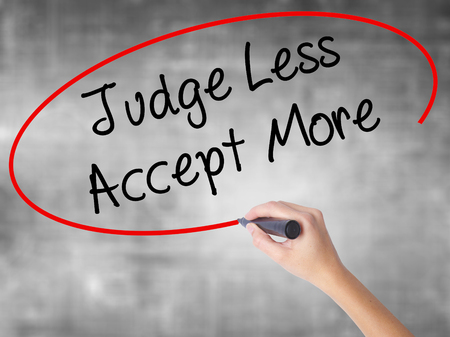 Woman Hand Writing Judge Less Accept More with black marker over transparent board. Isolated on grey. Business concept. Stock Photo