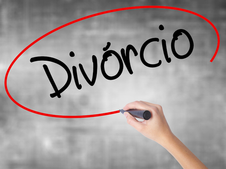 Woman Hand Writing Divorcio (Divorce in Portuguese) with black marker over transparent board. Isolated on grey. Business concept. Stock Photo