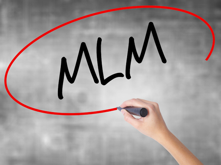 Woman Hand Writing  MLM (Multi-Level Marketing) with black marker over transparent board. Isolated on grey. Business concept. Stock Photo