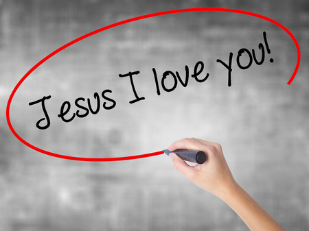 redemption: Woman Hand Writing Jesus I love you! with black marker over transparent board. Isolated on grey. Business concept. Stock Photo