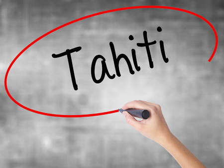 tahitian: Woman Hand Writing Tahiti with black marker over transparent board. Isolated on grey. Business concept. Stock Photo