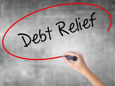 trouble free: Woman Hand Writing Debt Relief with black marker over transparent board. Isolated on grey. Business concept. Stock Photo