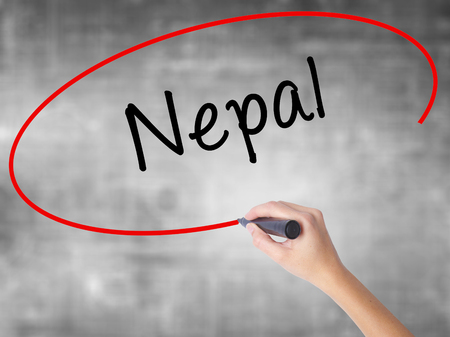 Woman Hand Writing Nepal  with black marker over transparent board. Isolated on grey. Business concept. Stock Photo