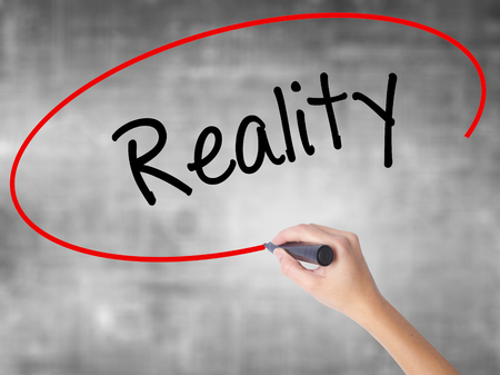 business skeptical: Woman Hand Writing  Reality with black marker over transparent board. Isolated on grey. Business concept. Stock Photo Stock Photo