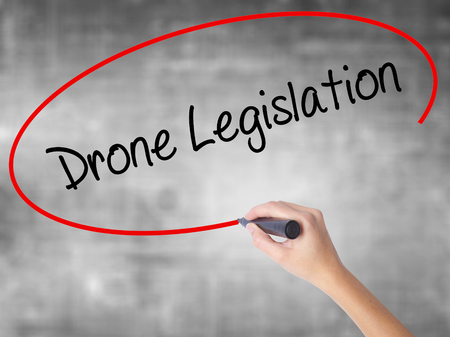 Woman Hand Writing Drone Legislation with black marker over transparent board. Isolated on grey. Business concept. Stock Photo