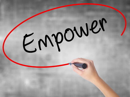 Woman Hand Writing Empower with black marker over transparent board. Isolated on grey. Business concept. Stock Photo