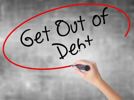 Woman Hand Writing Get Out of Debt with black marker over transparent board. Isolated on grey. Business concept. Stock Photo