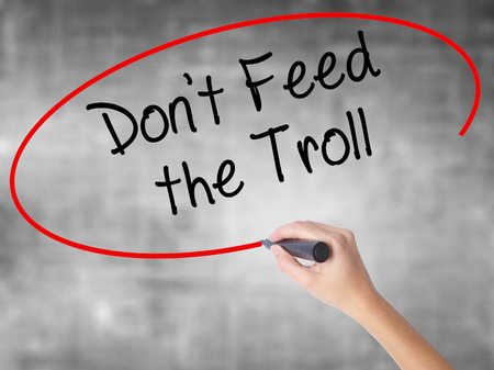 instigator: Woman Hand Writing Dont Feed the Troll with black marker over transparent board. Isolated on grey. Business concept. Stock Photo