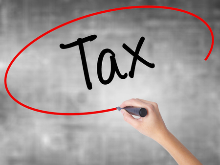 Woman Hand Writing Tax with black marker over transparent board. Isolated on grey. Business concept. Stock Photo