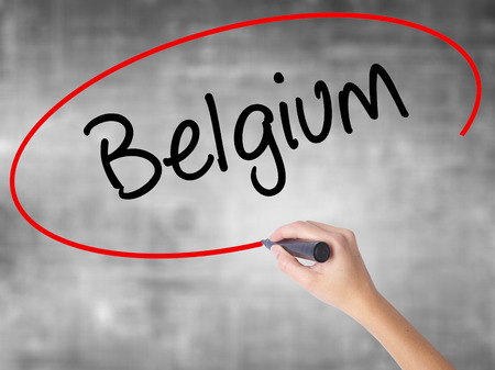 Woman Hand Writing Belgium  with black marker over transparent board. Isolated on grey. Business concept. Stock Photo Stock Photo