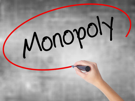 monopolio: Woman Hand Writing Monopoly with black marker over transparent board. Isolated on grey. Business concept. Stock Photo