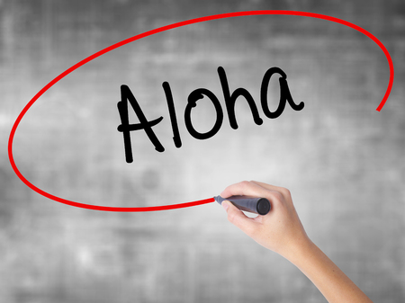 Woman Hand Writing Aloha  with black marker over transparent board. Isolated on grey. Business, technology, internet concept. Stock Photo