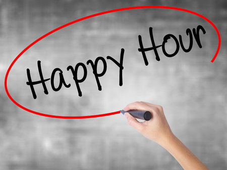 happyhour: Woman Hand Writing Happy Hour with black marker over transparent board. Isolated on grey. Business concept. Stock Photo