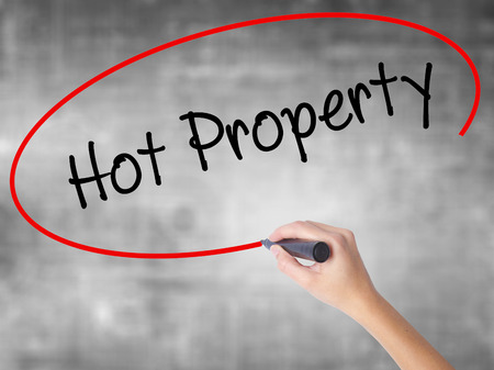 popularity: Woman Hand Writing Hot Property with black marker over transparent board. Isolated on grey. Business concept. Stock Photo