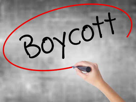 denying: Woman Hand Writing Boycott with black marker over transparent board. Isolated on grey. Business concept. Stock Photo
