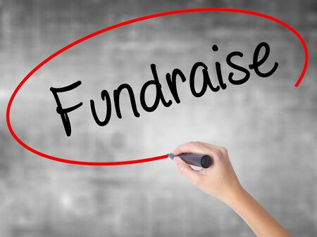 Woman Hand Writing Fundraise with black marker over transparent board. Isolated on grey. Business,  technology, internet concept. Stock Photo