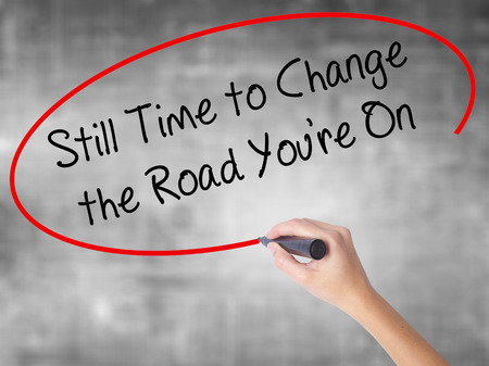 next horizon: Woman Hand Writing Still Time to Change the Road Youre On with black marker over transparent board. Isolated on grey. Business concept. Stock Photo Stock Photo