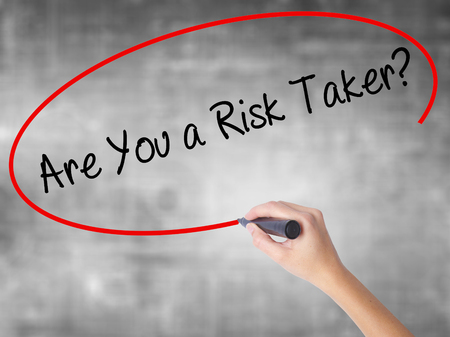 taker: Woman Hand Writing Are You a Risk Taker? with black marker over transparent board. Isolated on grey. Business concept. Stock Photo