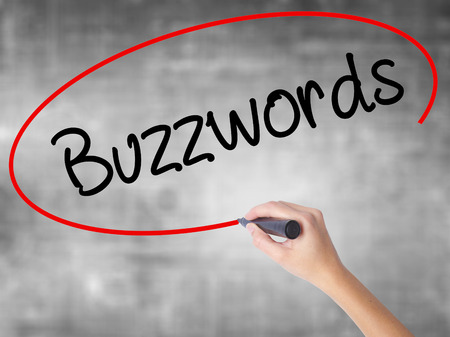 Woman Hand Writing Buzzwords with black marker over transparent board. Isolated on grey. Business concept. Stock Photo