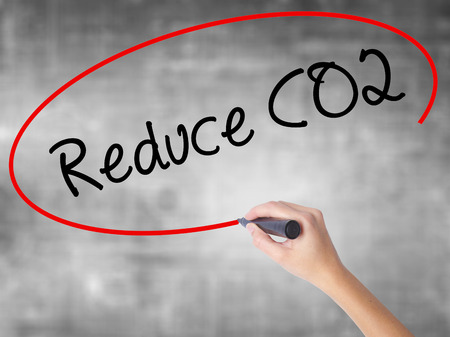 Woman Hand Writing Reduce CO2 with black marker over transparent board. Isolated on grey. Business concept. Stock Photo Imagens