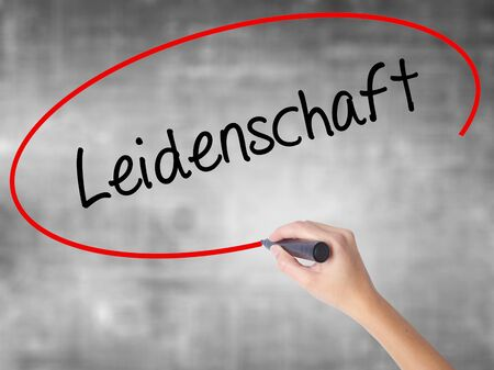 Woman Hand Writing Leidenschaft (Passion in German)  with black marker over transparent board. Isolated on grey. Business concept. Stock Photo