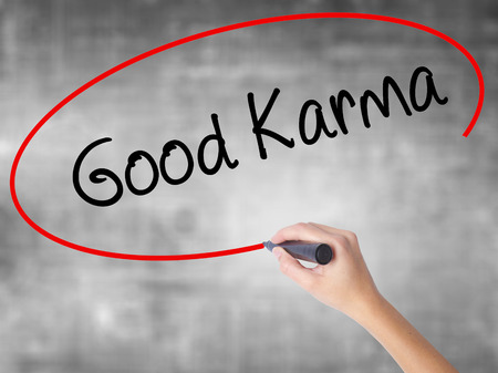 Woman Hand Writing  Good Karma with black marker over transparent board. Isolated on grey. Business concept. Stock Photo