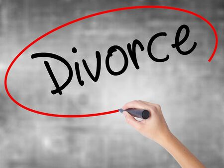 Woman Hand Writing Divorce  with black marker over transparent board. Isolated on grey. Business concept. Stock Photo Stock Photo
