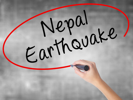Woman Hand Writing Nepal Earthquake with black marker over transparent board. Isolated on grey. Business concept. Stock Photo