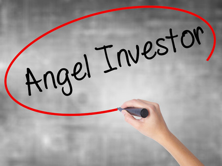 Woman Hand Writing Angel Investor with black marker over transparent board. Isolated on grey. Business concept. Stock Photo Stock Photo
