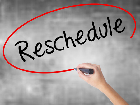 rescheduling: Woman Hand Writing Reschedule  with black marker over transparent board. Isolated on grey. Business concept. Stock Photo Stock Photo