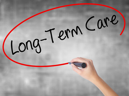 Woman Hand Writing Long-Term Care with black marker over transparent board. Isolated on grey. Business concept. Stock Photo Stock Photo