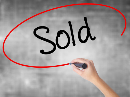 Woman Hand Writing Sold with black marker over transparent board. Isolated on grey. Business concept. Stock Photo