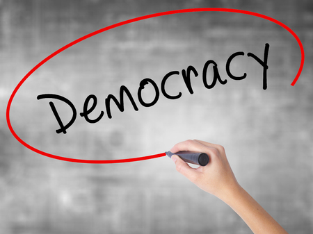 Woman Hand Writing Democracy with black marker over transparent board. Isolated on grey. Business concept. Stock Photo