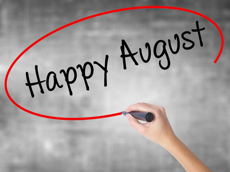 Woman Hand Writing Happy August with black marker over transparent board. Isolated on grey. Business concept. Stock Photo Stock Photo