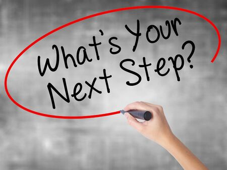 Woman Hand Writing Whats Your Next Step? with black marker over transparent board. Isolated on grey. Travel technology, internet concept. Stock Image Stock Photo