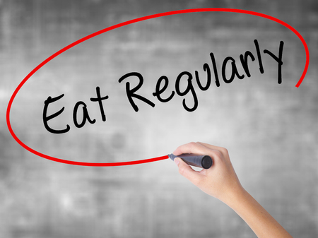 excrete: Woman Hand Writing Eat Regularly with black marker over transparent board. Isolated on grey. Business concept. Stock Photo Stock Photo