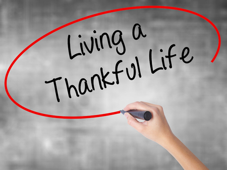 humility: Woman Hand Writing Living a Thankful Life with black marker over transparent board. Isolated on grey. Business, technology, internet concept.