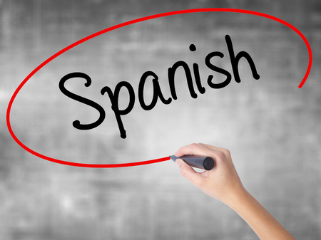 spaniard: Woman Hand Writing Spanish with black marker over transparent board. Isolated on grey. Business concept. Stock Photo Stock Photo
