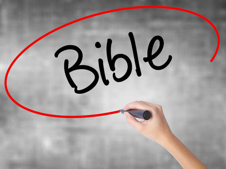 vangelo aperto: Woman Hand Writing Bible with black marker over transparent board. Isolated on grey. Business concept. Stock Photo