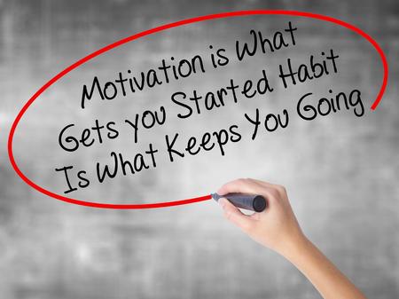 Frau Hand schreiben Motivation ist was Sie begonnen hat Gewohnheit ist, was Sie mit schwarzen Marker über transparente Bord geht. Getrennt auf Grau. Unternehmenskonzept. Foto auf Lager