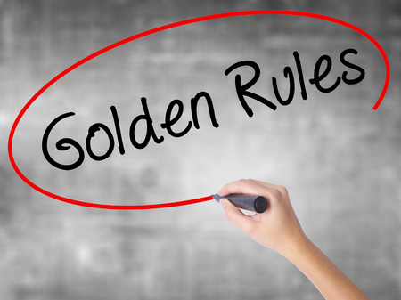 Woman Hand Writing Golden Rules with black marker over transparent board. Isolated on grey. Business concept. Stock Photo