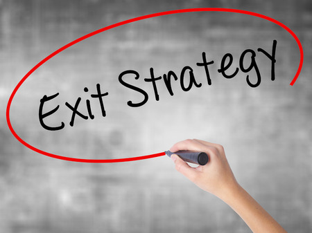 exiting: Woman Hand Writing Exit Strategy with black marker over transparent board. Isolated on grey. Business concept. Stock Photo