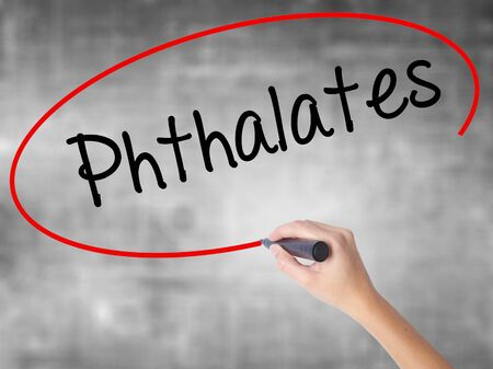 phthalates: Woman Hand Writing  Phthalates  with black marker over transparent board. Isolated on grey. Business concept. Stock Photo