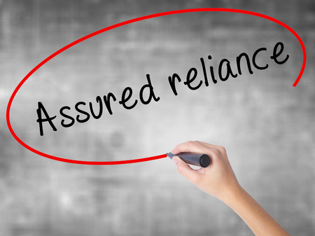 Man Hand writing Assured reliance with black marker on visual screen. Isolated on white. Business, technology, internet concept. Stock Image